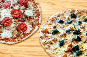 Dvě pizzy čerstvě vytažené z pece na dřevo